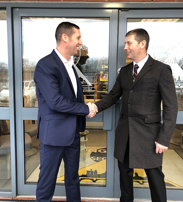 Alan Lingwood Snr & Jnr shaking hands outside the company head office
